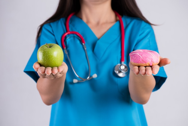Doktorfrauenhand, die donut und grünen apfel hält