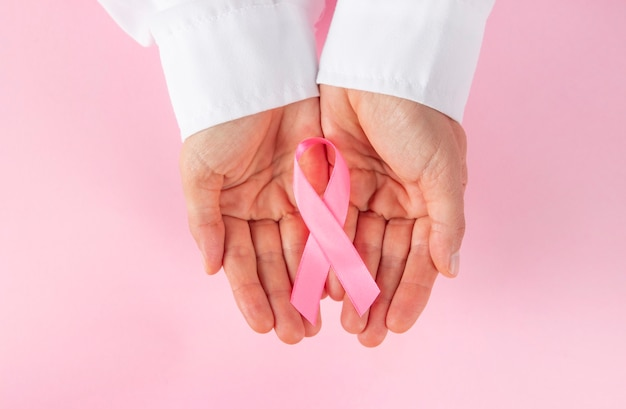 Doktorhände, die ein rosa bewusstseinsband auf einem rosa hintergrund halten