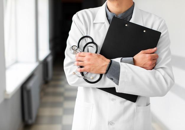 Doktorhände, die klemmbrett und stethoskop halten