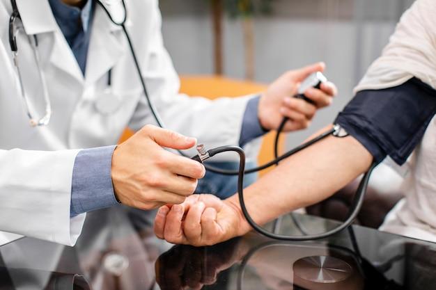 Doktorhände, die spannung zu einem patienten messen