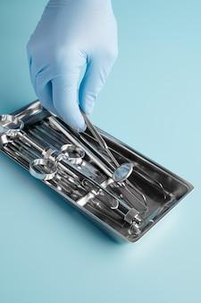 Doktorhände in blauen handschuhen, die professionelle zahnarztwerkzeuge am blauen tisch nehmen