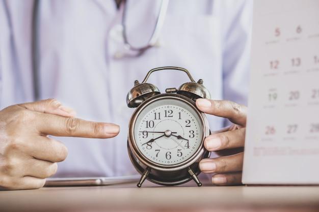 Doktorhand, die den wecker zeigt, der die zeit zeigt