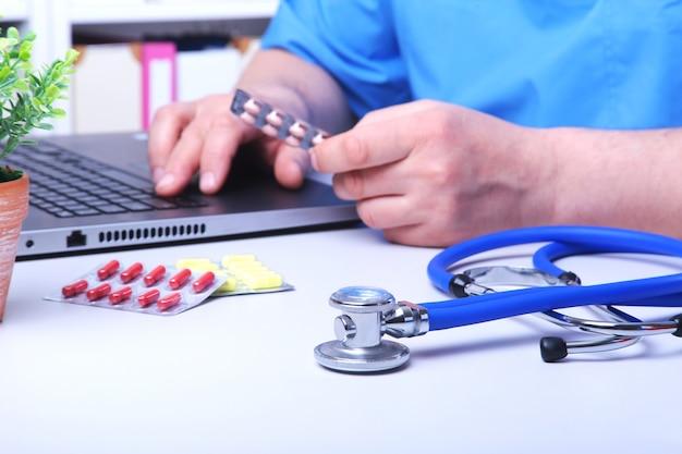 Doktorhand, die drogenkästen am büro-desktop zeigt. gesundheitswesen-, medizin- und apotheken-konzept.