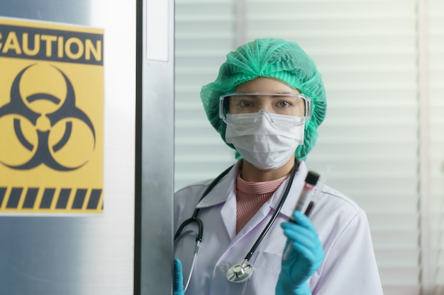 Doktorhand, die eine blutprobe des reagenzglases innen am biogefährdungszeichen auf tiefkühltruhe hält