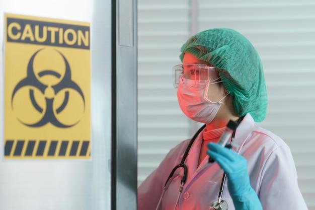 Doktorhand, die eine blutprobe des reagenzglases innen am biogefährdungszeichen auf tiefkühltruhe hält.
