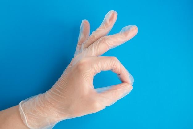 Doktorhand in medizinischem latexhandschuh, der ok-zeichen auf dem blauen hintergrund macht