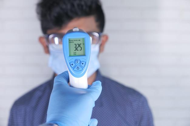 Doktorhand mit thermometer, das die temperatur eines mannes prüft