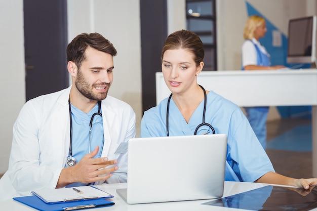Doktorkollegen, die laptop bei der diskussion verwenden