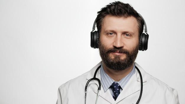 Doktorkopfhörer positiv lächelnder manndoktor mit kopfhörern auf weißem hintergrund, der kamera betrachtet