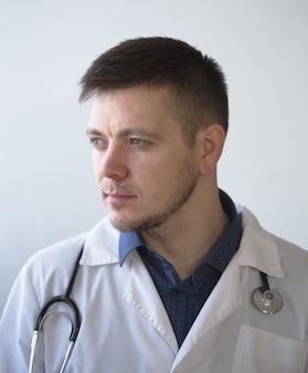 Doktormann, der am laptop computer schreibt, während er am schreibtisch an seinem arbeitsplatz sitzt. perfekter medizinischer service in der klinik. daten in medizin und gesundheitswesen