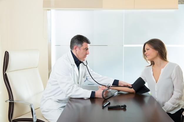 Doktormann, der blutdruckmanschette auf frauenpatienten überprüft