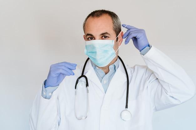 Doktormann, der schutzmaske und handschuhe drinnen trägt. corona-virus-konzept