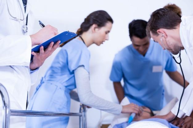 Doktorschreiben auf klemmbrett und anderem doktor, die einen patienten im krankenhaus überprüfen