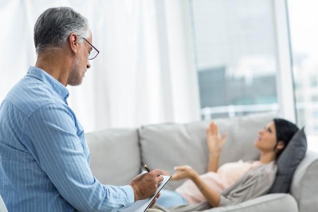 Doktorschreiben auf notizblock bei schwangere frau zu hause konsultieren