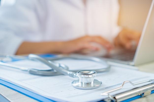 Doktorschreiben und arbeitslaptop-computer, schreibensverordnungsklemmbrett mit stethoskop schreibend