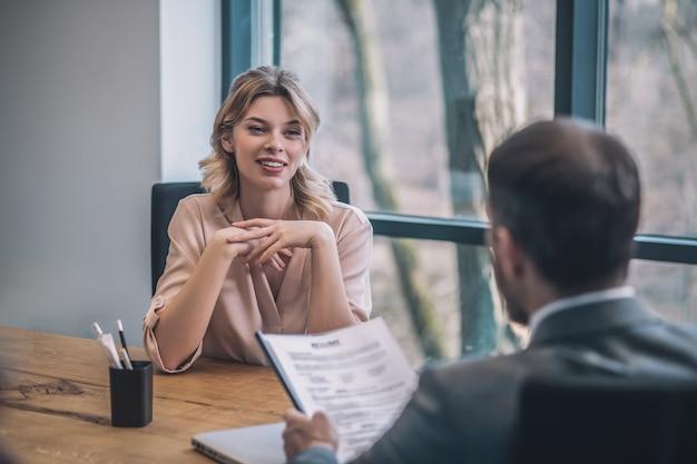 Dokument, analyse. blonde junge lächelnde geschäftsfrau und mann, die dokument studieren, das mit zurück zur kamera im hellen büro sitzt