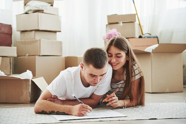 Dokument einreichen. fröhliches junges paar in ihrer neuen wohnung. konzeption des umzugs.