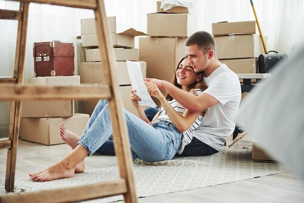 Dokument lesen. fröhliches junges paar in ihrer neuen wohnung. konzeption des umzugs.