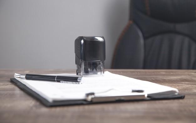 Dokument, stift und stempel auf dem tisch.