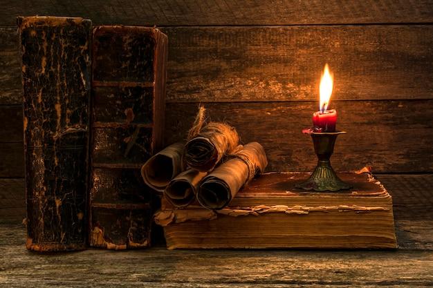 Dokumente, große schäbige bücher, eine sterbende kerze in einem kerzenständer auf einem alten holzhintergrund.