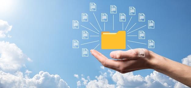Dokumentenmanagementsystem dms. geschäftsmann hält ordner- und dokumentsymbol. software zum archivieren, suchen und verwalten von unternehmensdateien und -informationen. internet-technologiekonzept. digitale sicherheit.