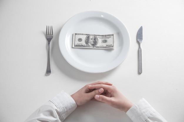 Dollar auf einem teller mit gabel und messer