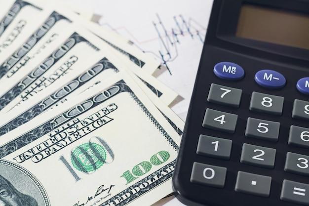 Dollar-banknoten und taschenrechner über verschwommenem handelsdiagramm. finanz-, buchhaltungs- oder sparkonzept.