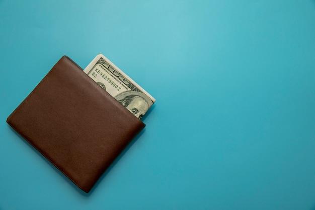 Dollar in den braunen beuteln gelegt auf ein blau