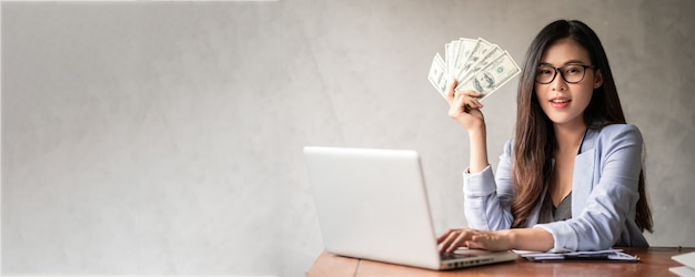 Dollar in der hand einer geschäftsfrau. eine asiatische frau arbeitet von zu hause oder vom büro aus und freut sich, geld von der arbeit und von einer zusätzlichen karriere oder einer teilzeit-selbstständigkeit zu bekommen.