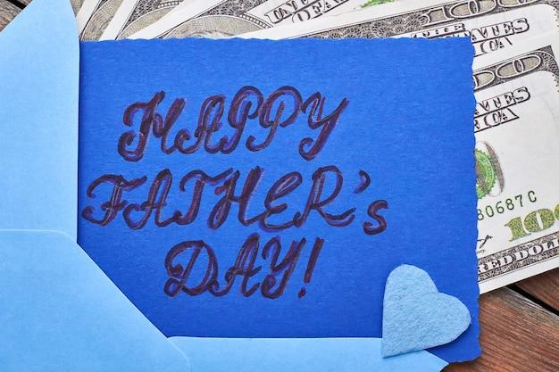 Dollar in der nähe der vatertagskarte. blaues stoffherz auf karte. finanzielle unterstützung für papa.