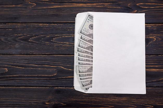 Dollar in einem weißen umschlag auf einem hölzernen hintergrund mit kopienraum.