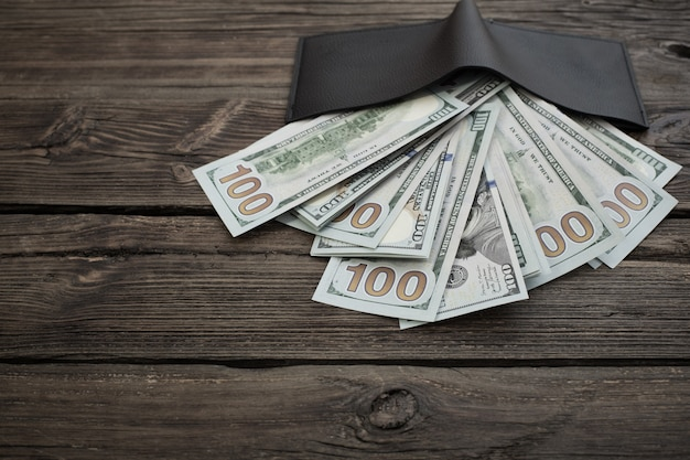 Dollar in schwarzer brieftasche auf altem hölzernem hintergrund