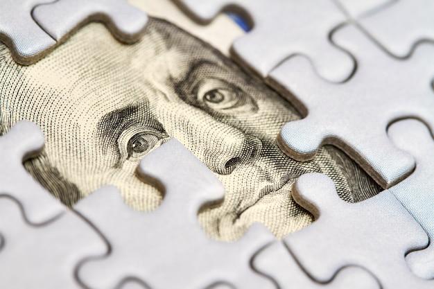 Dollar-puzzle, geschäftskonzept der lösung. dollarschein und puzzleteile. porträt des amerikanischen präsidenten franklin. nahaufnahme, selektiver fokus