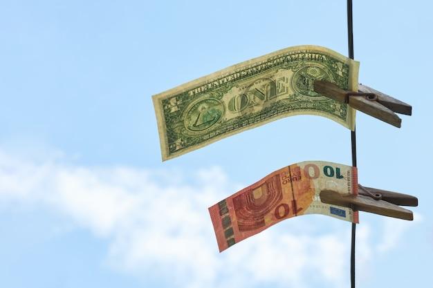 Dollar und euro hängen an einem seil