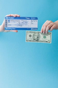 Dollar und flugticket in der frauenhand auf einem blauen hintergrund. reisekonzept, kopierraum