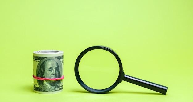 Dollar und lupe. suche nach investitionsquellen und sponsoren.