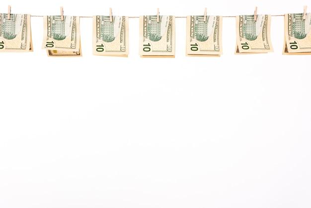 Dollarbanknoten, die an der wäscheleine hängen