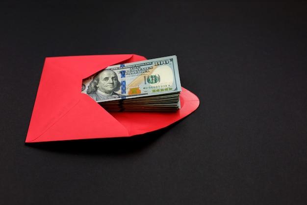 Dollargeld im roten umschlag auf schwarzem