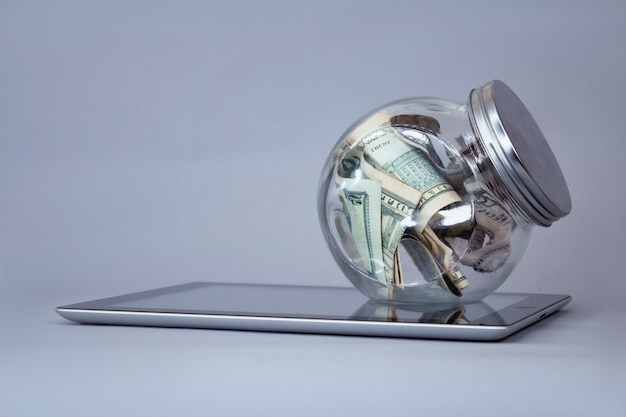 Dollarnoten in einem sparschwein aus glas auf einer tablette.