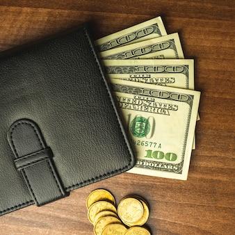 Dollarnoten mit cents in schwarzer lederbrieftasche, holztischhintergrund, geschäfts- und finanzkonzept, foto von oben