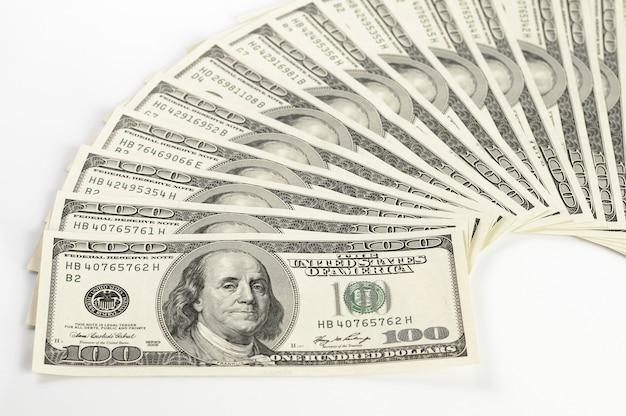 Dollarnoten wunderschön auf einem weißen tisch ausgelegt. us-dollar auf weißem hintergrund. finanzierungskonzept und wechselkurse. investitions- und gewinnkonzept