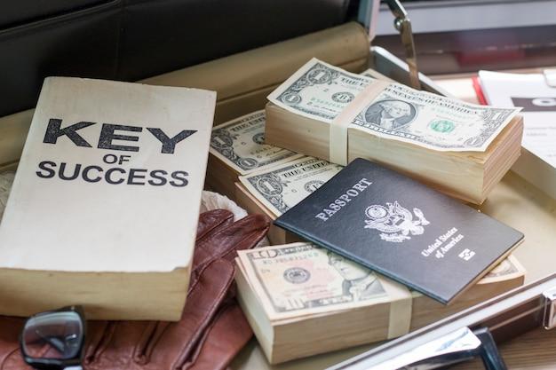 Dollarschein, pass, geschäftsdokument und schlüssel des erfolgsbuches auf tasche.