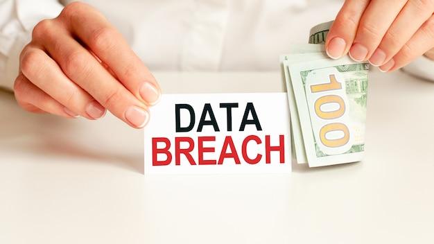 Dollarschein, weißes notizblockblatt an der weißen wand. data breach-text. finanz- und wirtschaftskonzept. finanzkonzept.