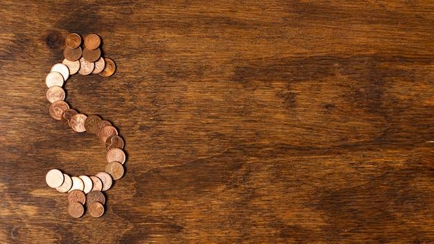 Dollarzeichen gemacht aus münzen heraus auf hölzernem hintergrund des kopienraumes