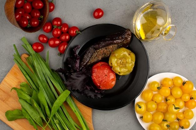 Dolma berühmte fleischmahlzeit aus dem osten in schwarzen teller zusammen mit frischen reifen gelben und roten tomaten und olivenöl