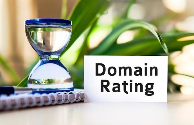 Domain-bewertungstext auf einem weißen notizbuch und einer sanduhr
