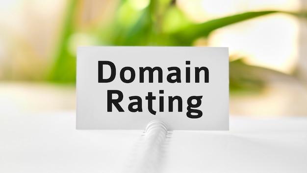 Domain-bewertungstext auf einem weißen notizbuch und grünen blumen
