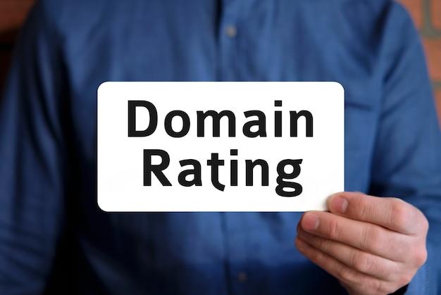 Domain-bewertungstext auf einem weißen zeichen in der hand eines mannes in einem blauen hemd