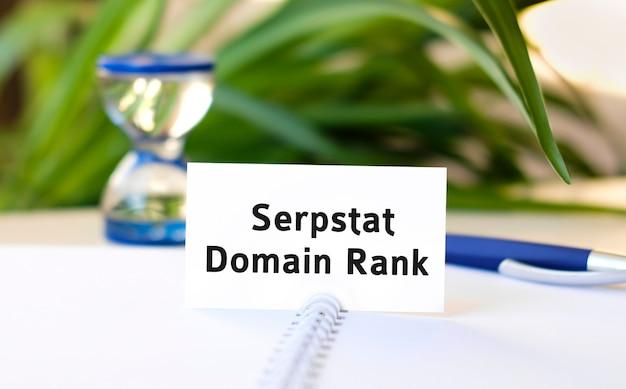 Domain-rang-seo-geschäftskonzepttext auf einem weißen notizbuch und einer sanduhr, einem blauen stift, grünen blumen
