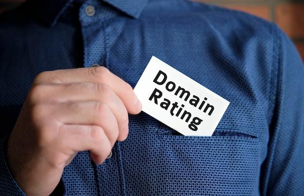 Domainbewertungstext auf einem weißen schild in der hand eines mannes im hemd